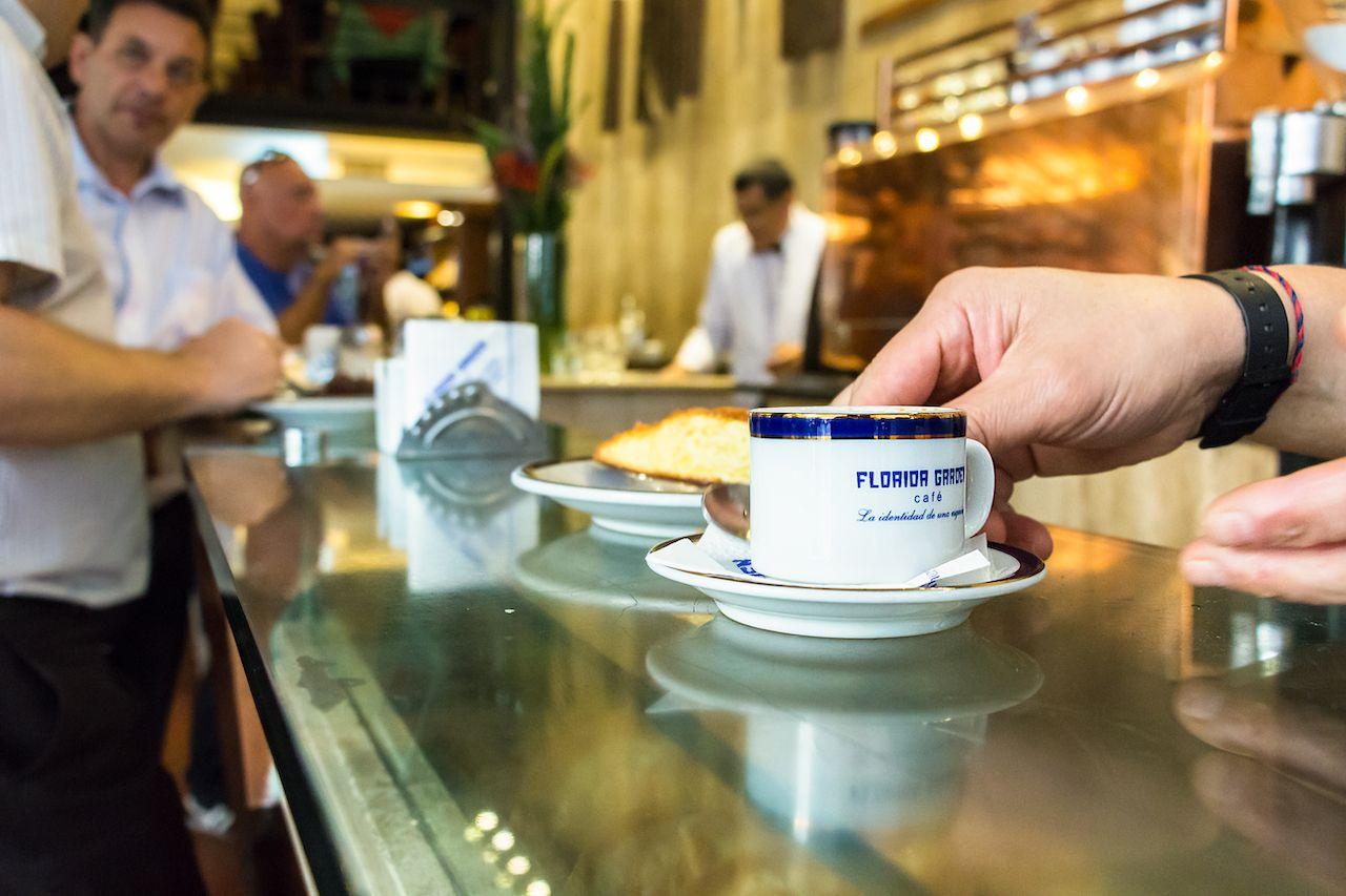 barista serving a cup of espresso coffee called Cortado at the counter of the Florida Garden Cafe, Buenos Aires
