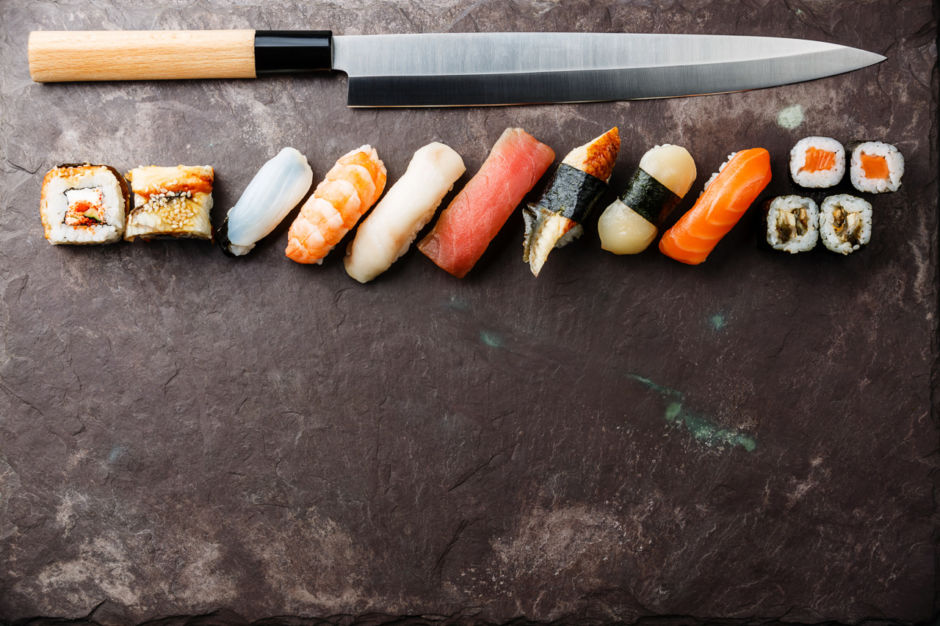Sushi rolls and nigiri with Japanese knife on stone slate background; Shutterstock ID 382660009; Purchase Order: ANA 2019 SP1