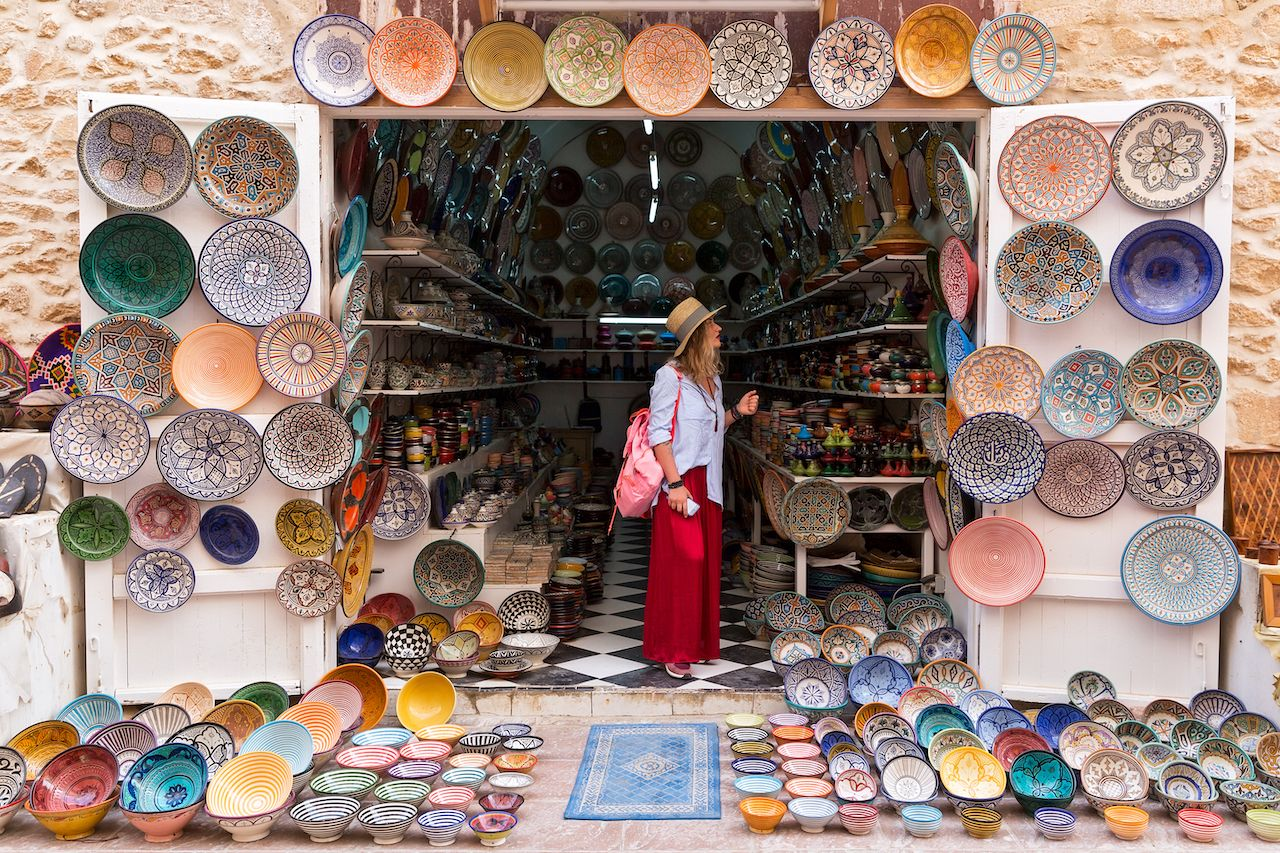 Person in long red skirt, hat and with pink backpack is standing in a small shop and looking at Moroccan colorful plates
