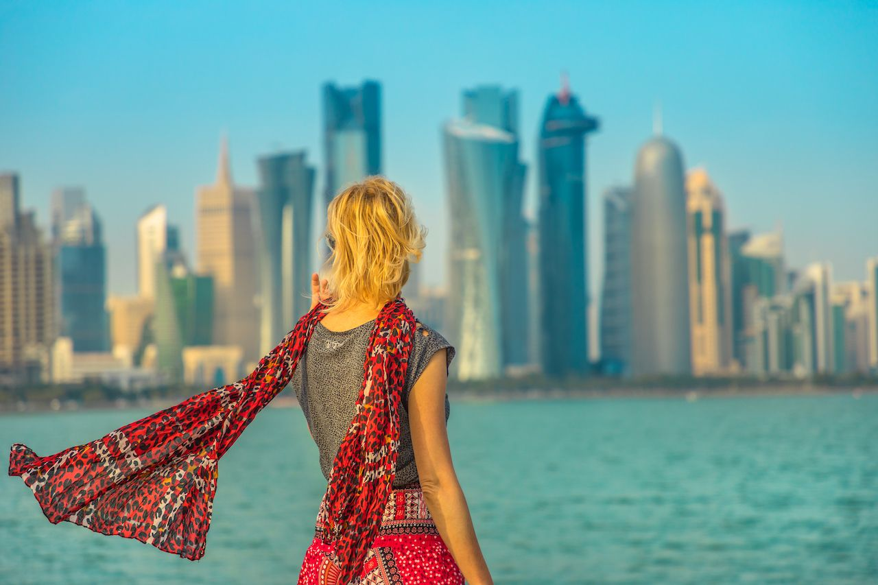 Person looking at modern skyscrapers of Doha West Bay