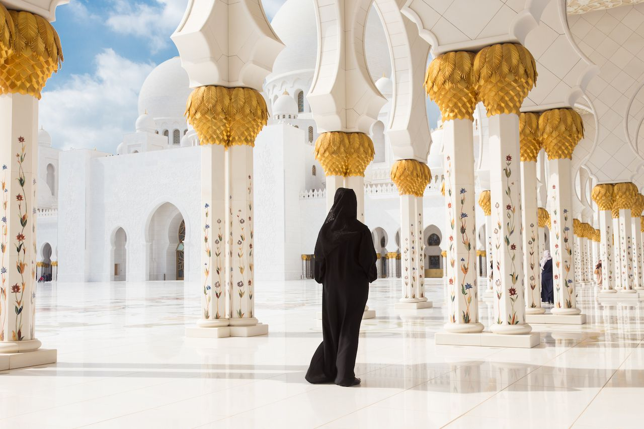 Traditionally dressed arabic woman wearing black burka wisiting Sheikh Zayed Grand Mosque in Abu Dhabi, United Arab Emirates