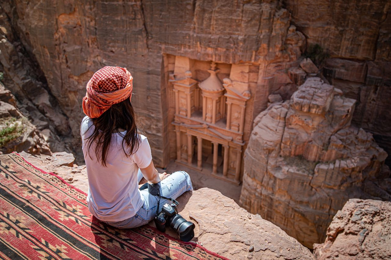 traveler sitting on carpet viewpoint in Petra