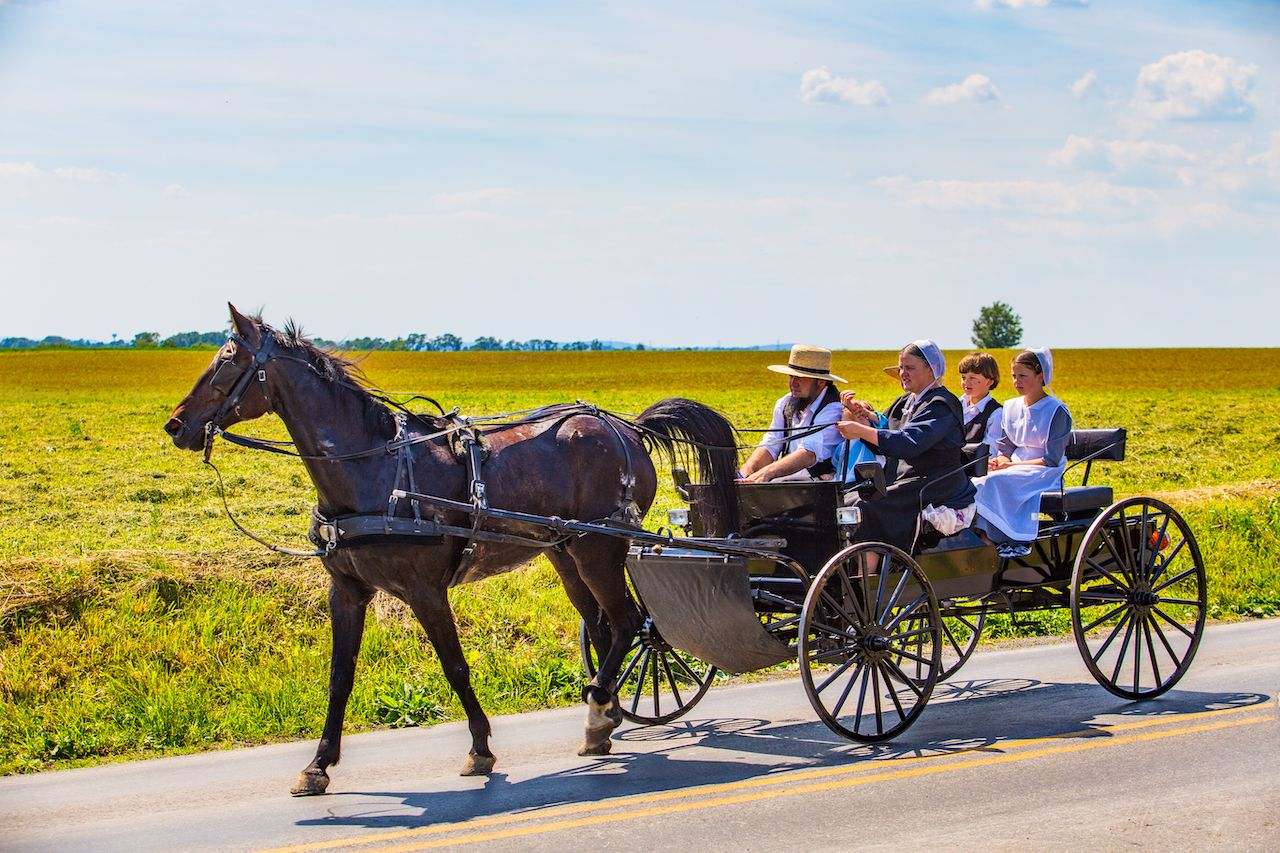 Amish family ride in an open wagon in Lancaster County, Pennsylvania