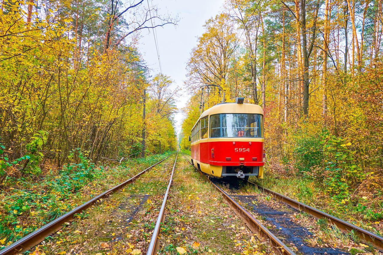 vintage red tram in forest corridor in Pushcha-Voditsa