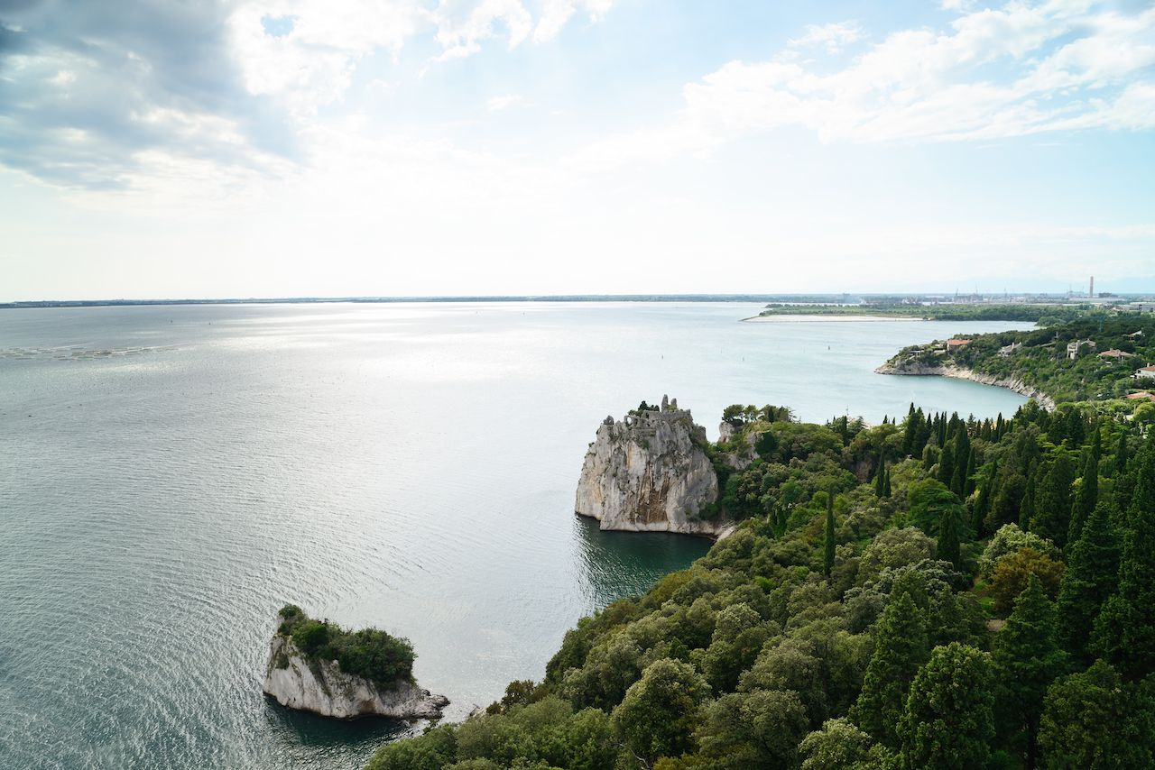 Adriatic sea with the ruins of the old Duino Castle near Trieste, Italy