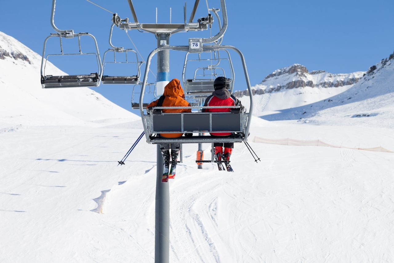 Two skiers go up on chair-lift