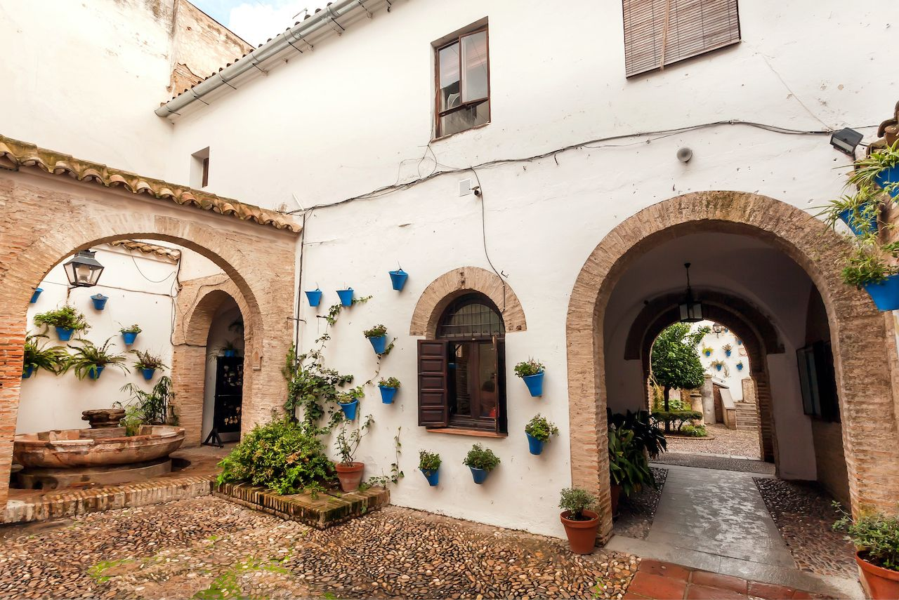 Arches of historical courtyard with flowerpots in town of Andalusia