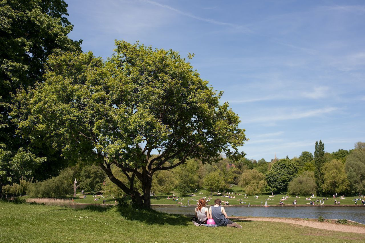 Couple relaxing on the grass in Hampstead Heath