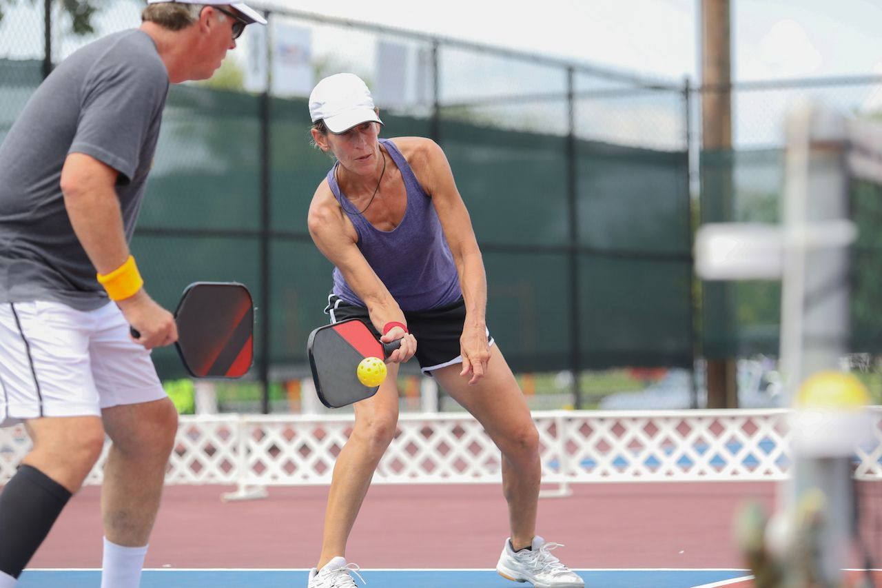 A mixed doubles team competes in a pickleball tournament
