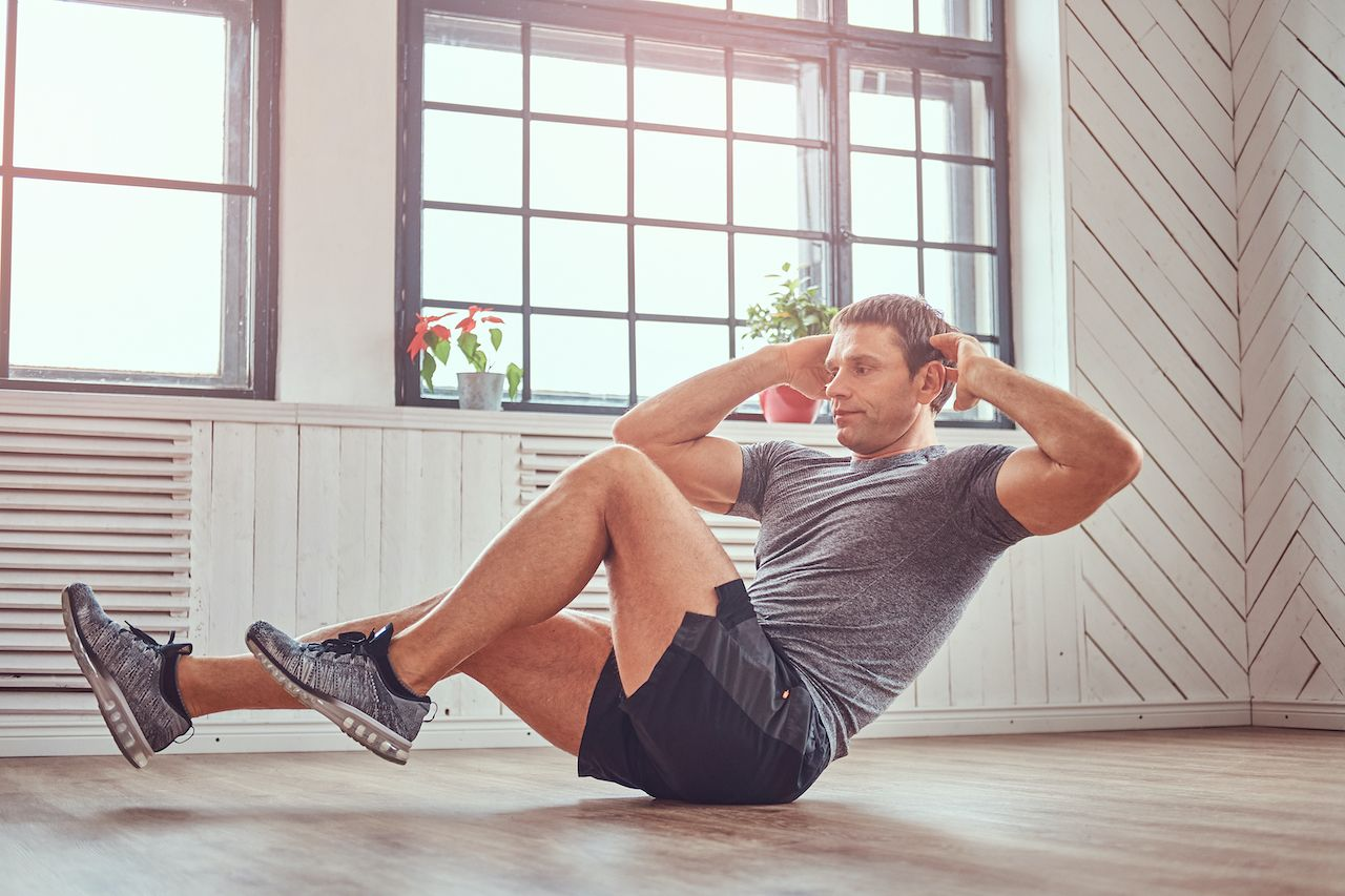 person abdominal exercises on floor at home