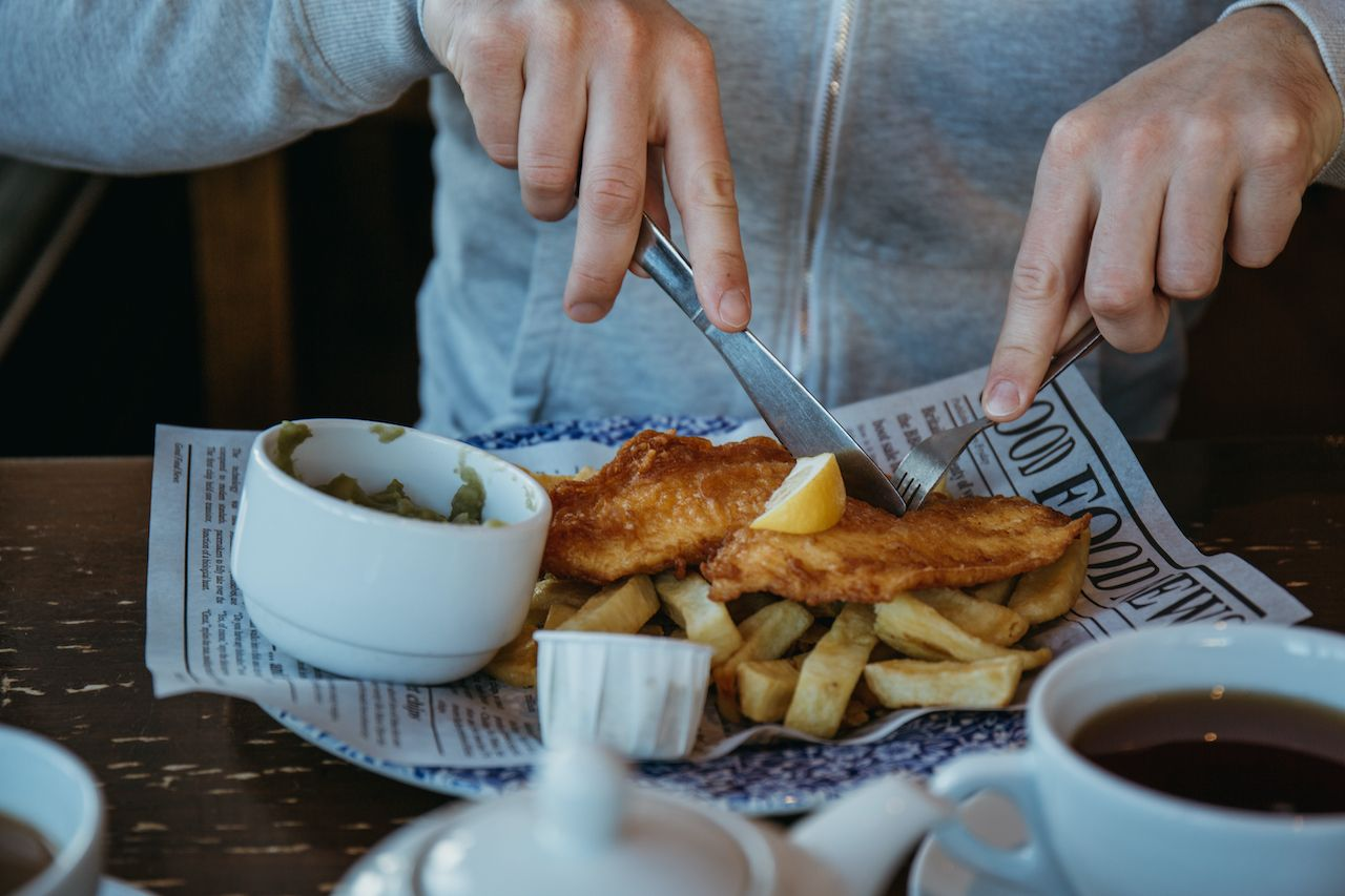 person sitting at the wooden table, eating fish and chips