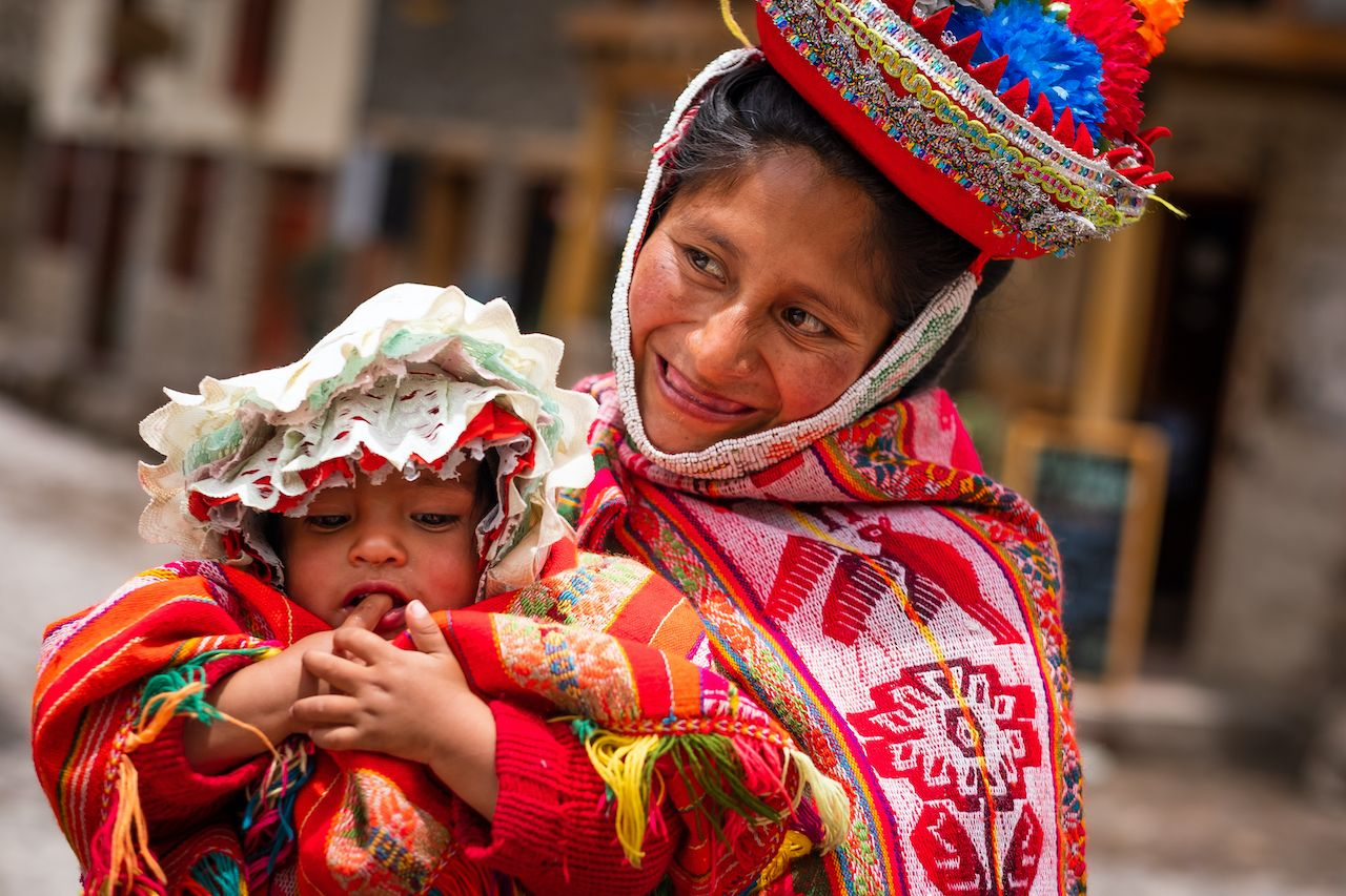 Mother in national colorful clothing holding little kid