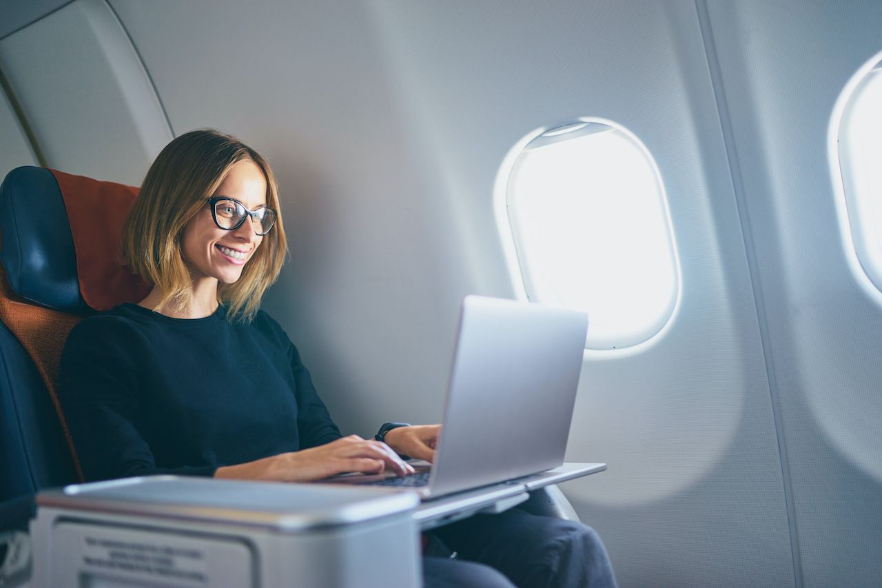 Person on laptop in airplane