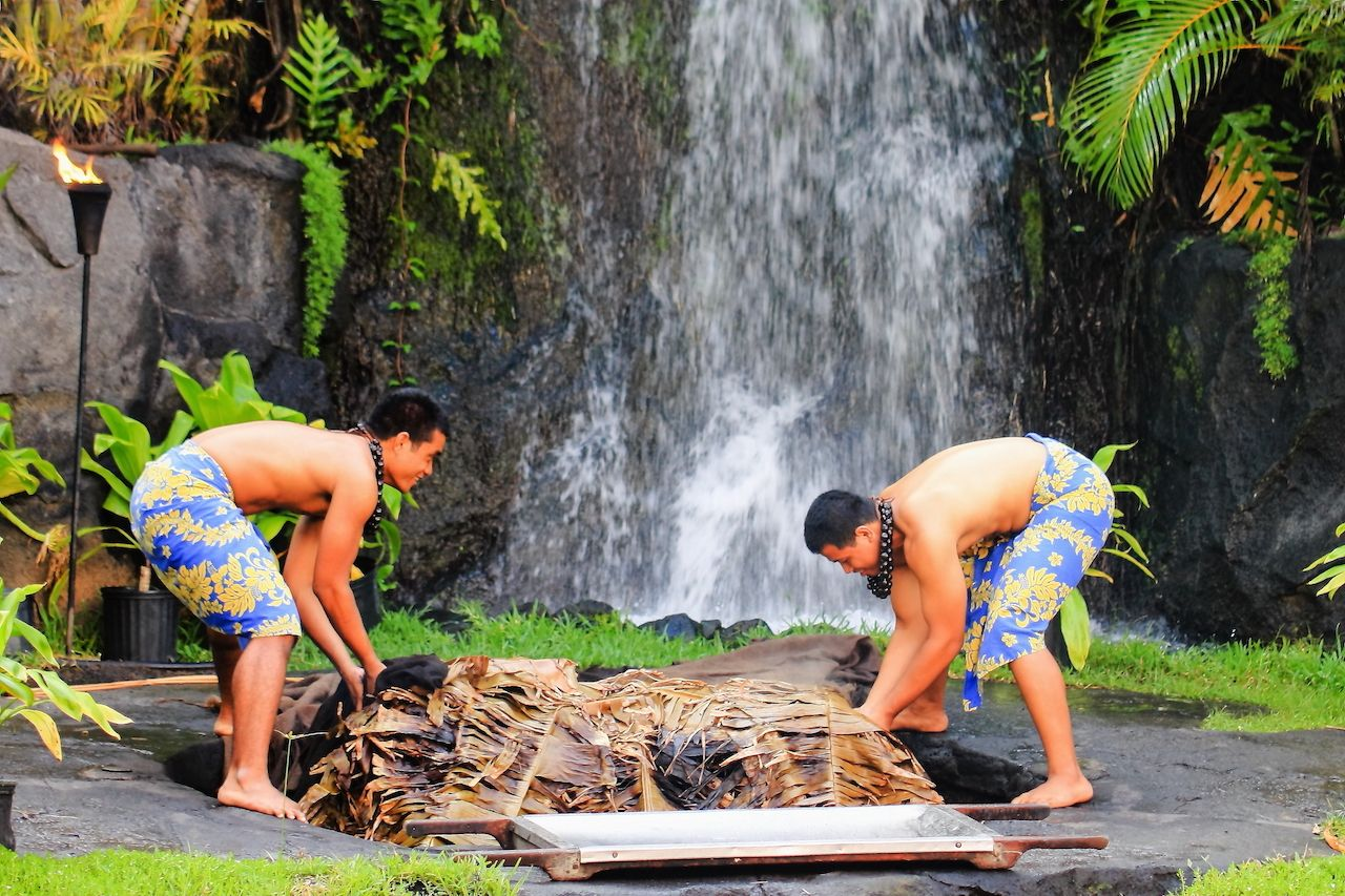 two people uplift a pig cooked in the traditional style Kalua