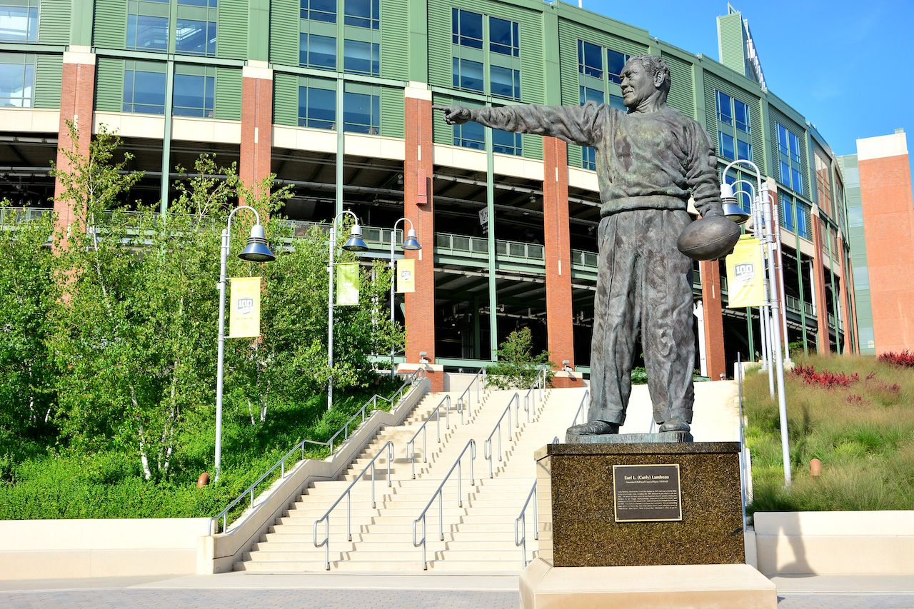 The stadium at Green Bay with the Earl L. (Curly) Lambeau bronze statue in front pointing the way to the entrance.