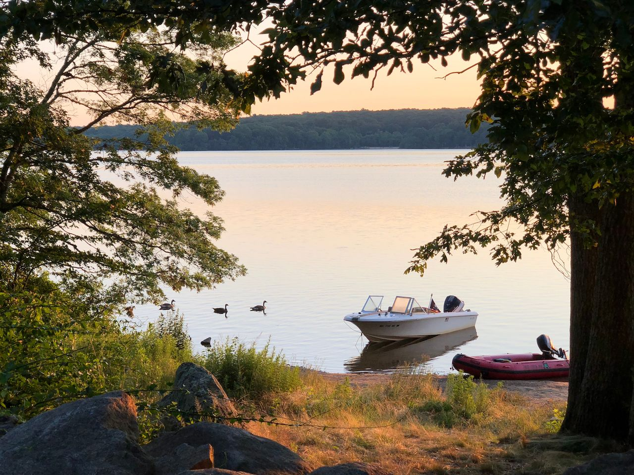 Two small boats at sunset at Watchaug Pond in Burlingame State Park, Charlestown. Rhode Island
