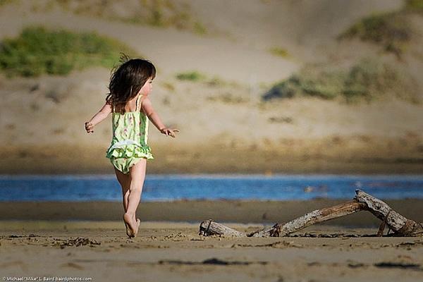 Small child runs on Morro Strand