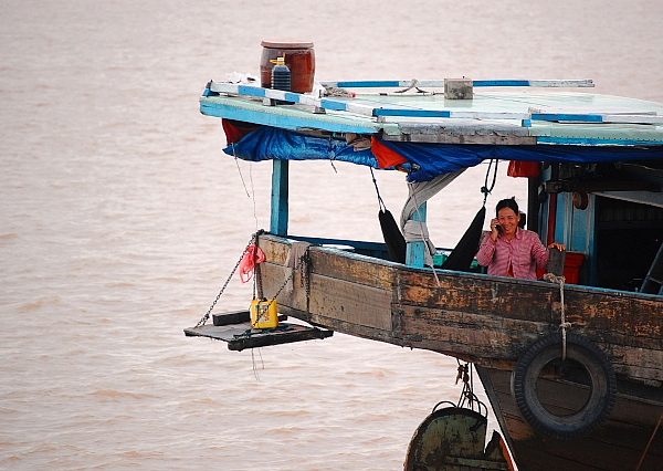 Woman using cell phone on the Mekong River, Cambodia