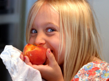 Kid eating peach