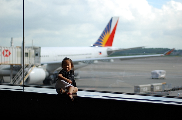 child playing at airport with plane in background