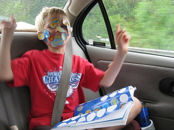 a boy covered with stickers acting silly in a car during a road trip