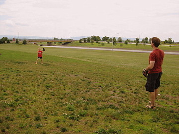 a family playing baseball to stretch their legs during a road trip