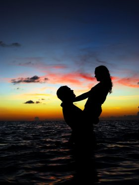 Couple embracing in the waves at sunset